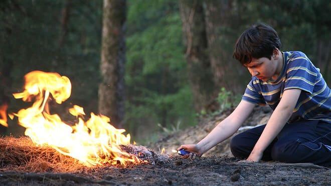 Мальчик поджигает костер