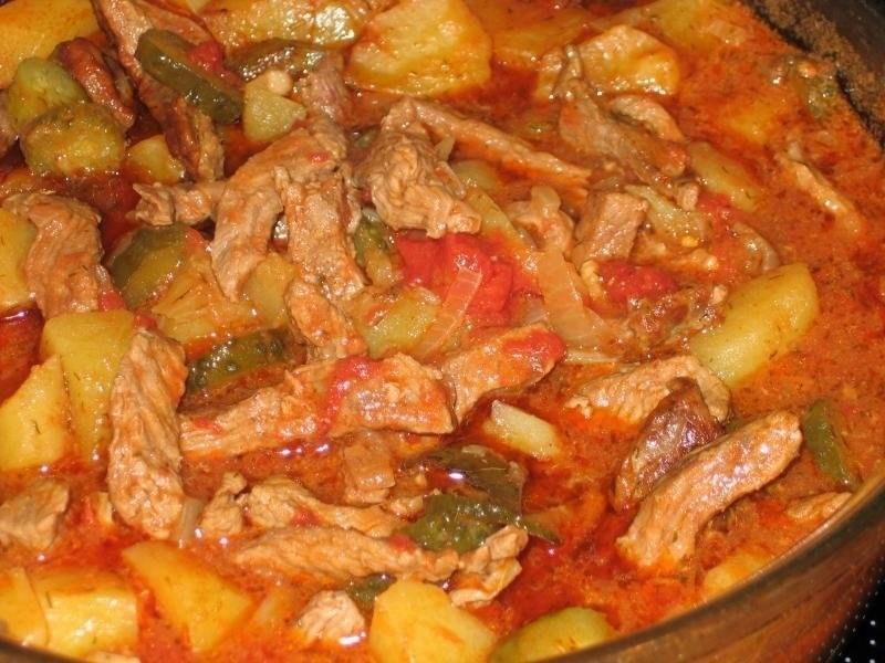 Пикантная свинина с томатами и маринованными огурцами - сытное блюдо, которое можно быстро приготовить в казане